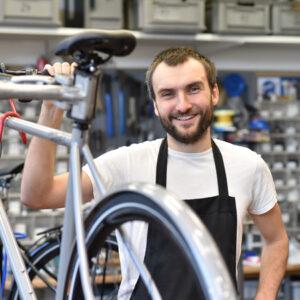 Mann an Fahrrad als Monteur